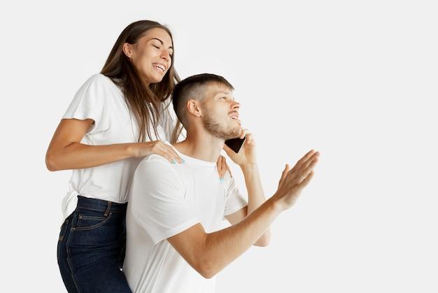 Retrato de la hermosa joven pareja aislado en la pared blanca. expresión facial, emociones humanas, concepto publicitario. hombre hablando por teléfono, la mujer quiere prestar atención a sí misma.
