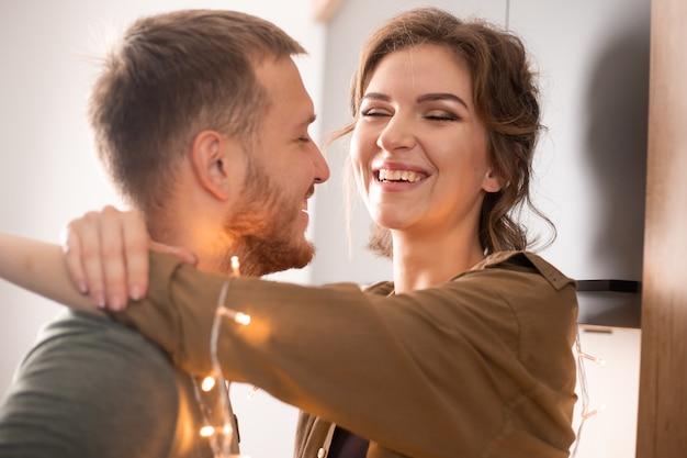 Retrato de hermosa joven pareja en ropa casual besándose y riendo