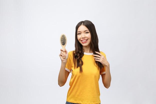 Retrato de una hermosa joven peine un cabello maravilloso