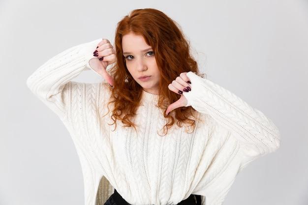 Retrato de una hermosa joven pelirroja que se encuentran aisladas sobre fondo blanco, apuntando a sí misma