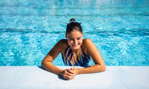 Retrato de hermosa joven posando en la piscina