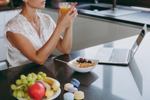 El retrato de la hermosa joven que trabaja con la computadora portátil mientras desayuna con cereales y leche y bebe jugo de naranja