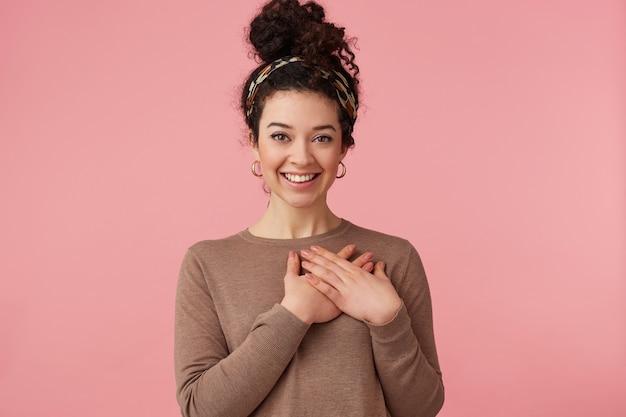 Retrato de una hermosa joven rizada, sonríe ampliamente con las manos al corazón, escuchando un cortesía, mirando a cámara aislada sobre fondo rosa.