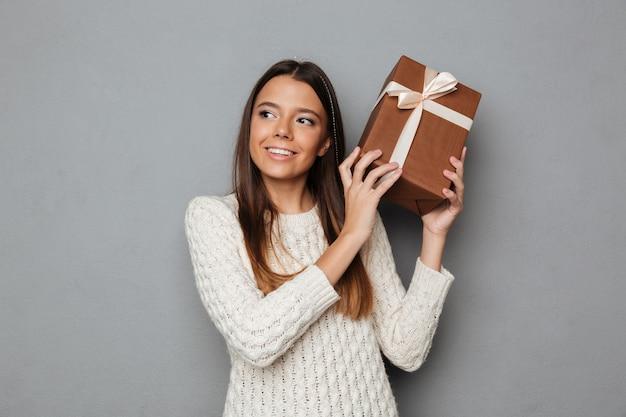 Retrato de una hermosa joven en suéter con presente