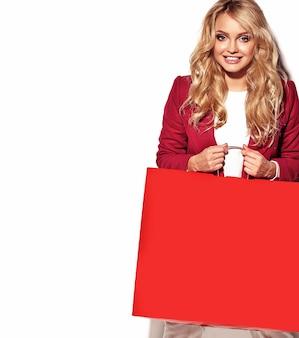 Retrato de hermosa linda feliz dulce mujer rubia sorprendida chica sosteniendo en sus manos gran bolsa de compras en ropa roja hipster aislado en blanco