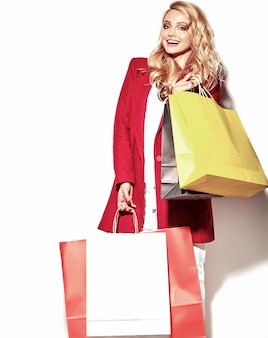 Retrato de hermosa linda feliz dulce mujer rubia sorprendida chica sosteniendo en sus manos una gran bolsa de compras en ropa roja hipster aislado en blanco