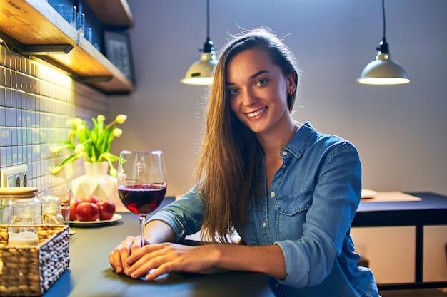 Retrato de hermosa linda joven casual sonriente feliz bebiendo mujer sosteniendo un vaso de vino tinto y sentado a la mesa en la cocina estilo loft en casa
