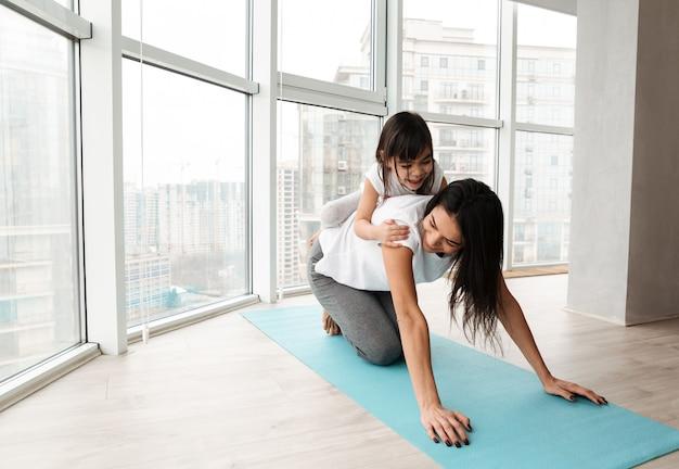 Retrato de la hermosa madre de familia y el niño divirtiéndose, mientras hacen ejercicios de fitness en la estera de yoga en casa
