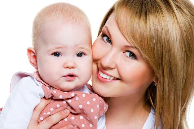 Retrato de una hermosa madre feliz con bebé aislado en blanco
