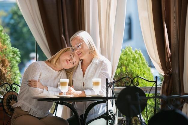 Retrato de hermosa madre madura y su hija sosteniendo la taza sentado en su casa