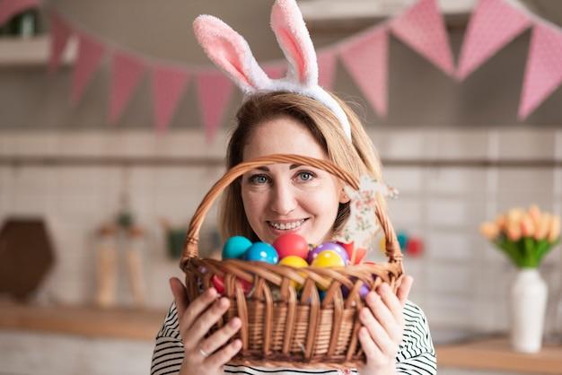 Retrato de hermosa madre sosteniendo una canasta con huevos
