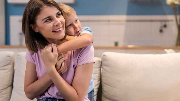 Retrato de hermosa mamá jugando con su hijo
