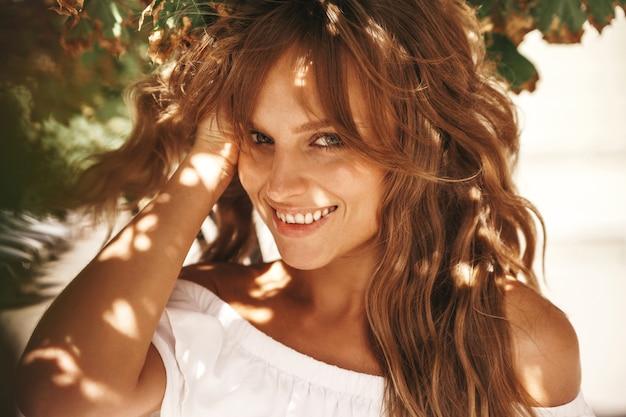 Retrato de la hermosa modelo de adolescente rubia linda sin maquillaje en ropa de vestido blanco hipster de verano posando en el fondo de la calle, tocando su cabello