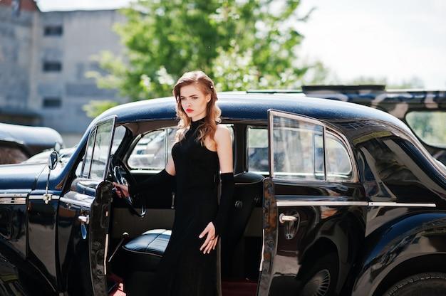 Retrato de la hermosa modelo de chica de moda sexy con maquillaje brillante en estilo retro cerca de coches antiguos