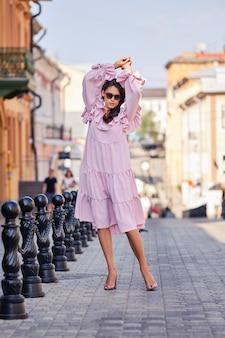 Retrato de hermosa modelo elegante en vestido rosa posando con las manos arriba
