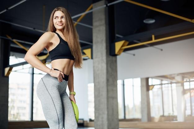 Retrato de hermosa modelo fitness posando sosteniendo un disco de peso con mancuernas en un amplio gimnasio moderno cuidando sus abdominales.