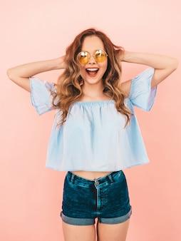 Retrato de hermosa modelo lindo sonriente en gafas de sol redondas. chica en ropa colorida de verano. modelo posando. jugando con su cabello