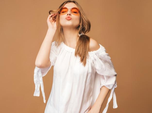 Retrato de hermosa modelo lindo sonriente con labios rosados. chica en vestido blanco de verano. modelo posando en gafas de sol. dar beso
