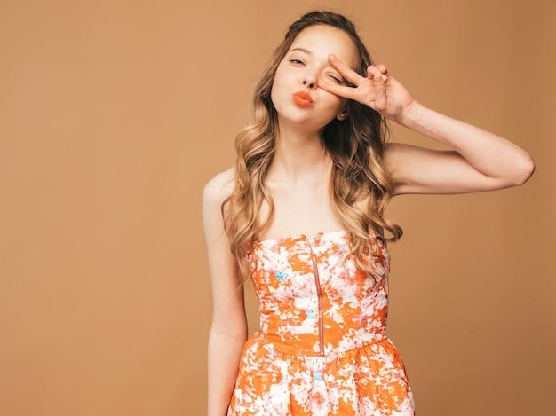 Retrato de hermosa modelo lindo sonriente con labios rosados. chica en vestido colorido de verano. modelo posando mostrando el signo de la paz y dando un beso