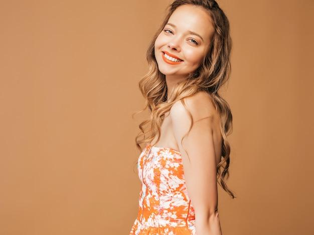 Retrato de hermosa modelo lindo sonriente con labios rosados. chica en vestido colorido de verano. modelo posando