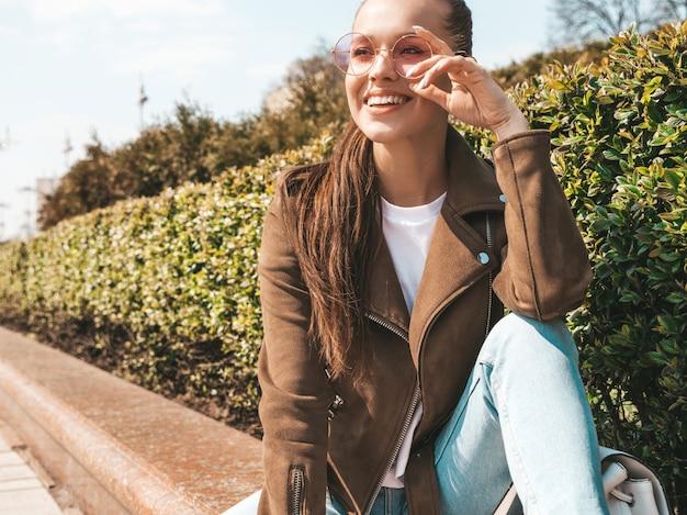 Retrato de la hermosa modelo morena sonriente vestida con chaqueta hipster de verano y ropa de jeans chica de moda sentada en el banco en la calle