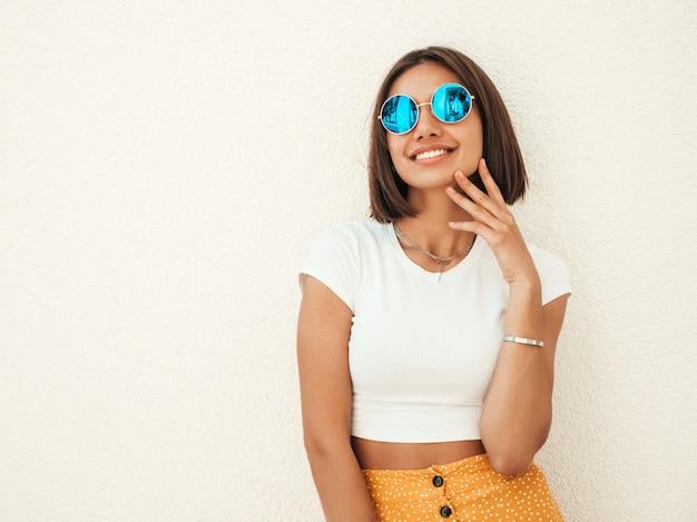 Retrato de la hermosa modelo morena sonriente vestida con ropa hipster de verano. chica de moda posando en la calle cerca de la pared blanca. mujer divertida y positiva divirtiéndose