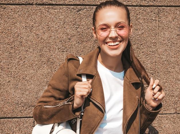 Retrato de la hermosa modelo morena sonriente vestida con ropa de jeans y chaqueta hipster de verano