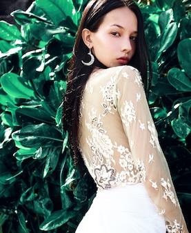 Retrato de la hermosa modelo de mujer caucásica con cabello largo y oscuro en pantalones clásicos de pierna ancha posando cerca de fondo verde tropical exótico deja