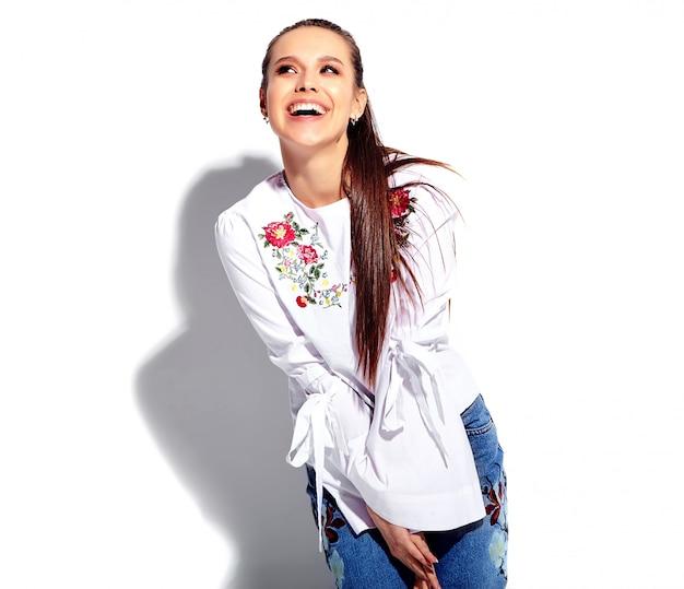 Retrato de la hermosa modelo de mujer morena caucásica sonriente en blusa blanca y elegantes jeans de verano con estampado de flores