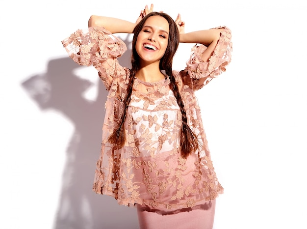 Retrato de la hermosa modelo de mujer morena caucásica sonriente con coletas dobles en ropa elegante de verano rosa brillante