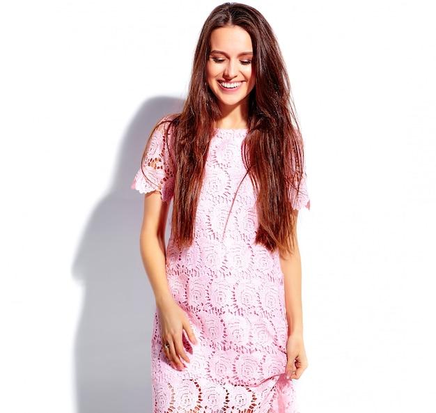 Retrato de la hermosa modelo de mujer morena caucásica sonriente en verano rosa brillante vestido elegante aislado sobre fondo blanco.
