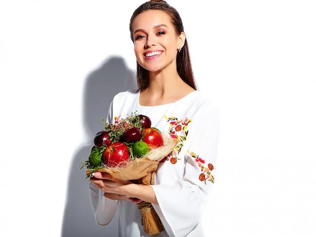 Retrato de hermosa modelo de mujer morena caucásica sonriente en vestido elegante de verano blanco con inusual ramo creativo de flores