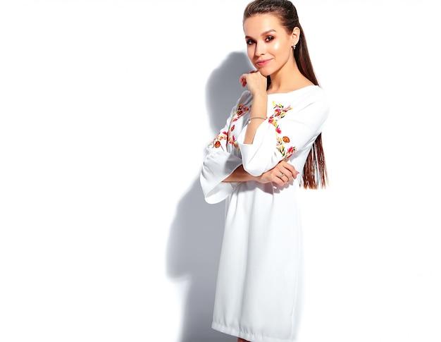 Retrato de la hermosa modelo de mujer morena caucásica sonriente en vestido elegante de verano blanco
