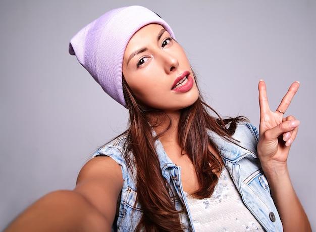 Retrato de la hermosa modelo de mujer morena linda en ropa casual de verano jeans sin maquillaje en gorro púrpura haciendo foto selfie en teléfono aislado en gris. mostrando signo de paz