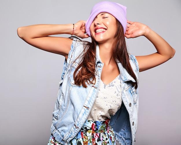 Retrato de la hermosa modelo de mujer morena linda sonriente en ropa casual de verano jeans sin maquillaje en gorro púrpura aislado en gris