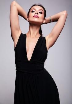 Retrato de la hermosa modelo de mujer morena sonriente en vestido negro con maquillaje de noche y labios rojos aislados en gris