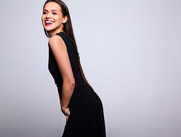 Retrato de hermosa modelo de mujer morena sonriente en vestido negro con maquillaje de noche y labios rojos aislados en gris