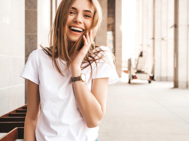 Retrato de la hermosa modelo rubia sonriente vestida con ropa hipster de verano.