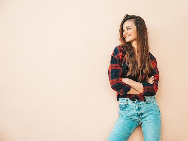 Retrato de hermosa modelo sonriente. mujer sexy vestida con jeans y camisa a cuadros de verano hipster. chica de moda posando junto a la pared en la calle