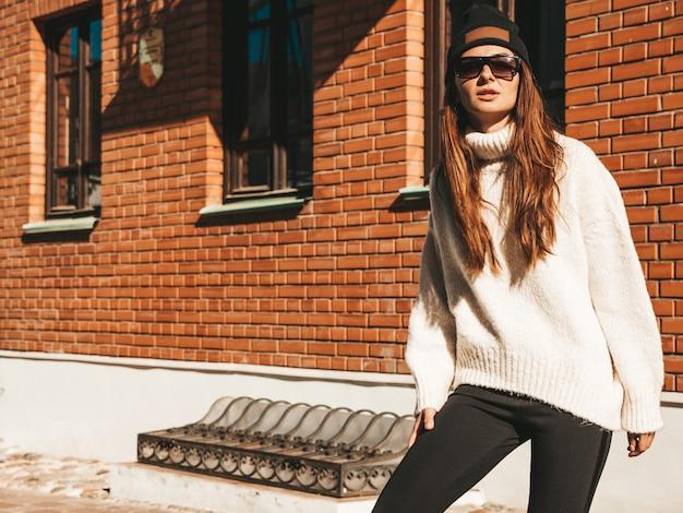 Retrato de hermosa modelo sonriente. mujer vestida con suéter blanco cálido hipster y gorro. chica de moda posando en la calle