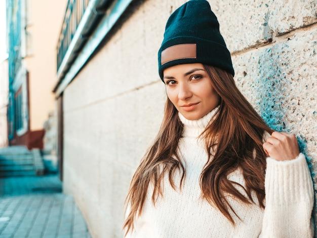 Retrato de hermosa modelo sonriente. mujer vestida con suéter blanco cálido hipster y gorro. ella posando en la calle