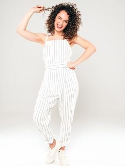 Retrato de la hermosa modelo sonriente con peinado afro rizos vestido con ropa hipster de verano. chica despreocupada sexy posando en estudio sobre fondo gris. moda mujer divertida y positiva muestra lengua