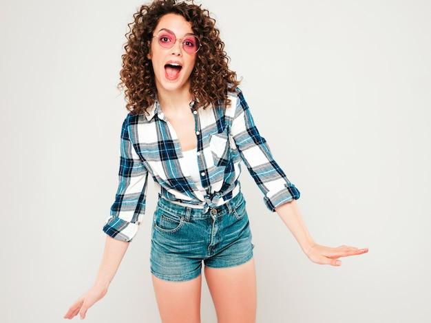 Retrato de hermosa modelo sonriente con peinado afro rizos vestido con ropa hipster de verano. chica despreocupada sexy posando en estudio sobre fondo gris. mujer divertida y positiva de moda