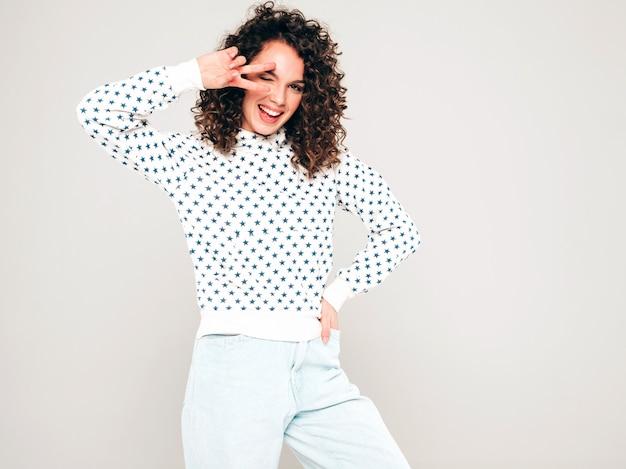 Retrato de hermosa modelo sonriente con peinado afro rizos vestido con ropa hipster de verano. chica despreocupada sexy posando sobre fondo gris. moda mujer divertida y positiva con capucha blanca