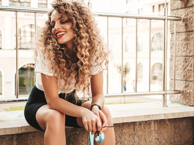 Retrato de hermosa modelo sonriente con peinado afro rizos vestido con ropa hipster de verano. chica despreocupada sexy sentada en el fondo de la calle. moda divertida y positiva mujer divirtiéndose