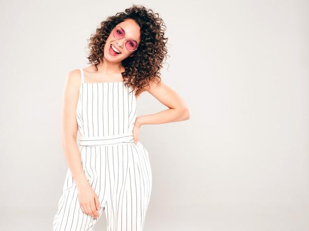 Retrato de hermosa modelo sonriente con peinado afro rizos vestido con ropa hipster de verano. mujer divertida y positiva de moda en gafas de sol