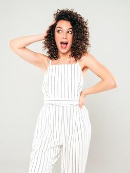 Retrato de hermosa modelo sonriente con peinado afro rizos vestido con ropa hipster de verano. mujer divertida y positiva de moda