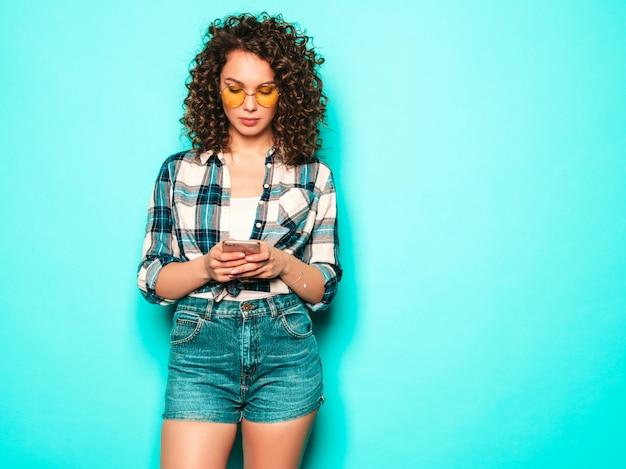 Retrato de hermosa modelo sonriente con peinado afro rizos vestido con ropa de verano. chica despreocupada posando cerca de la pared azul. la mujer usa su teléfono móvil y escribiendo sms. ella busca ventas en la tienda