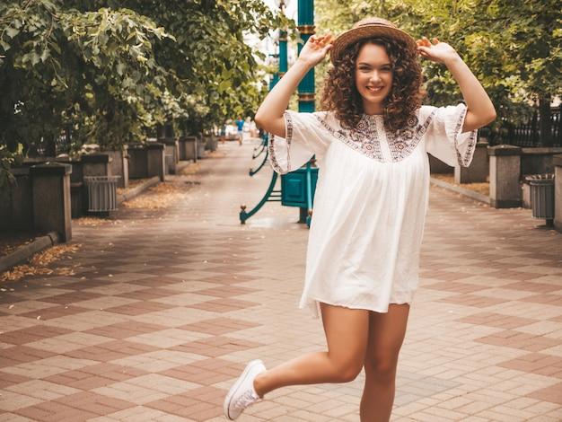 Retrato de hermosa modelo sonriente con peinado afro rizos vestido con vestido blanco hipster de verano.