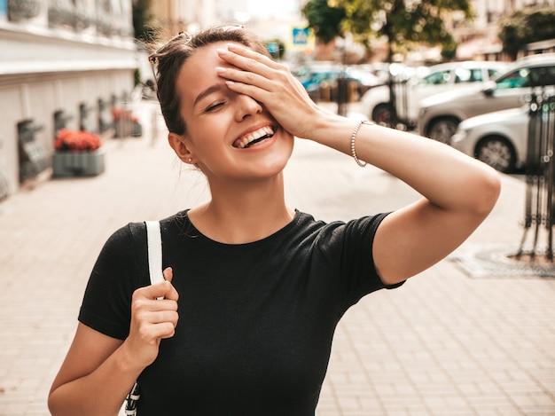 Retrato de hermosa modelo sonriente vestida con ropa de verano. chica de moda posando en la calle. mujer divertida y positiva divirtiéndose